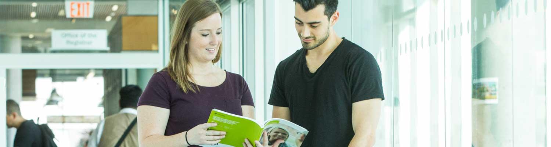 students reading a catalog