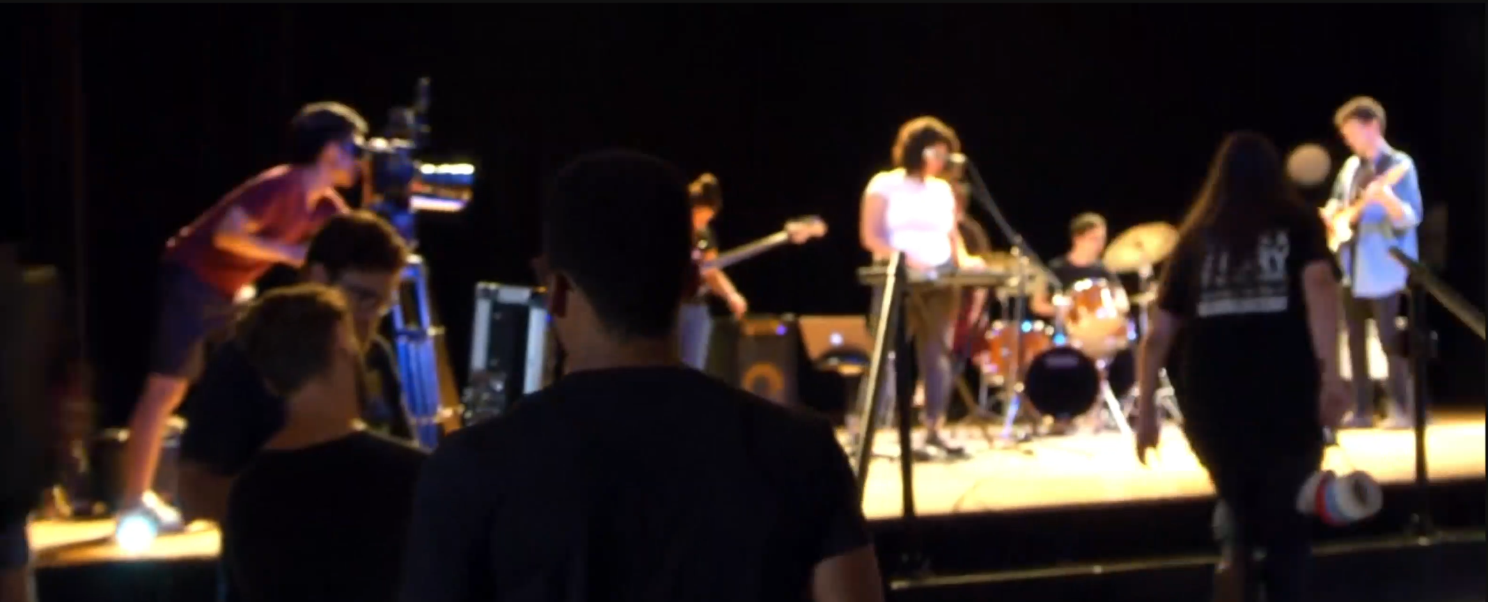 Blurred photo of a band performing on stage while being filmed.