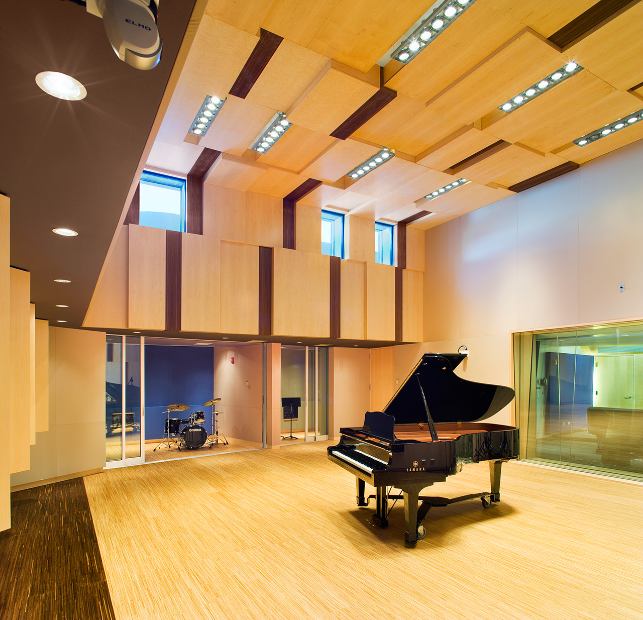 Wood panelled studio room with a grand piano in the center