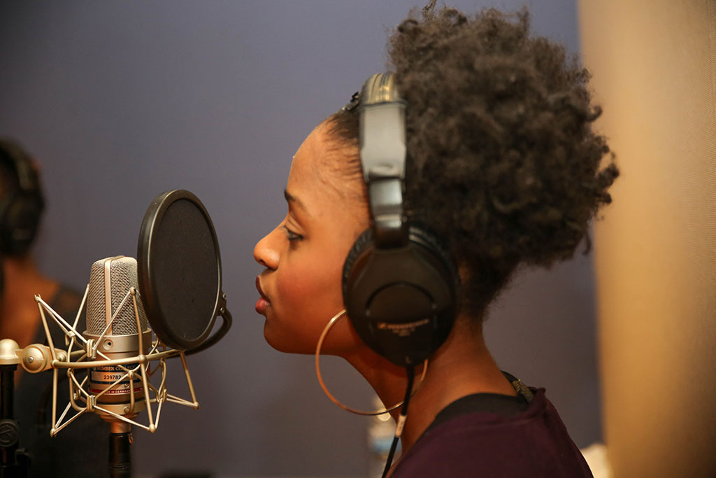 Young woman singing into a microphone