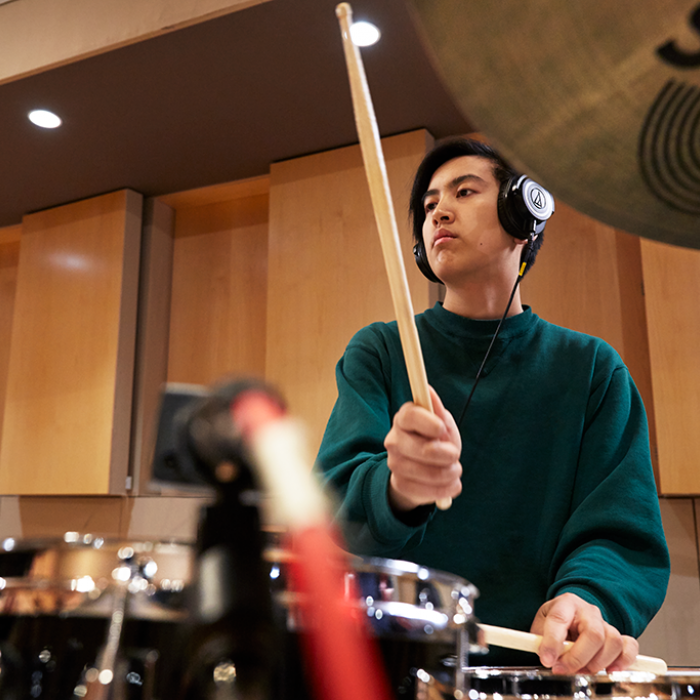 Young man playing drums while wearing headphones
