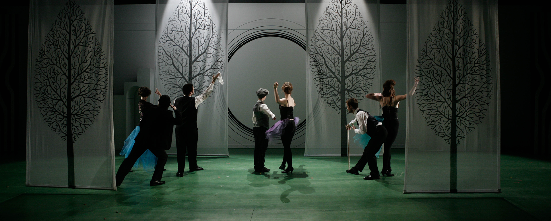 Seven performers on a stage with moody lighting and tree backdrops