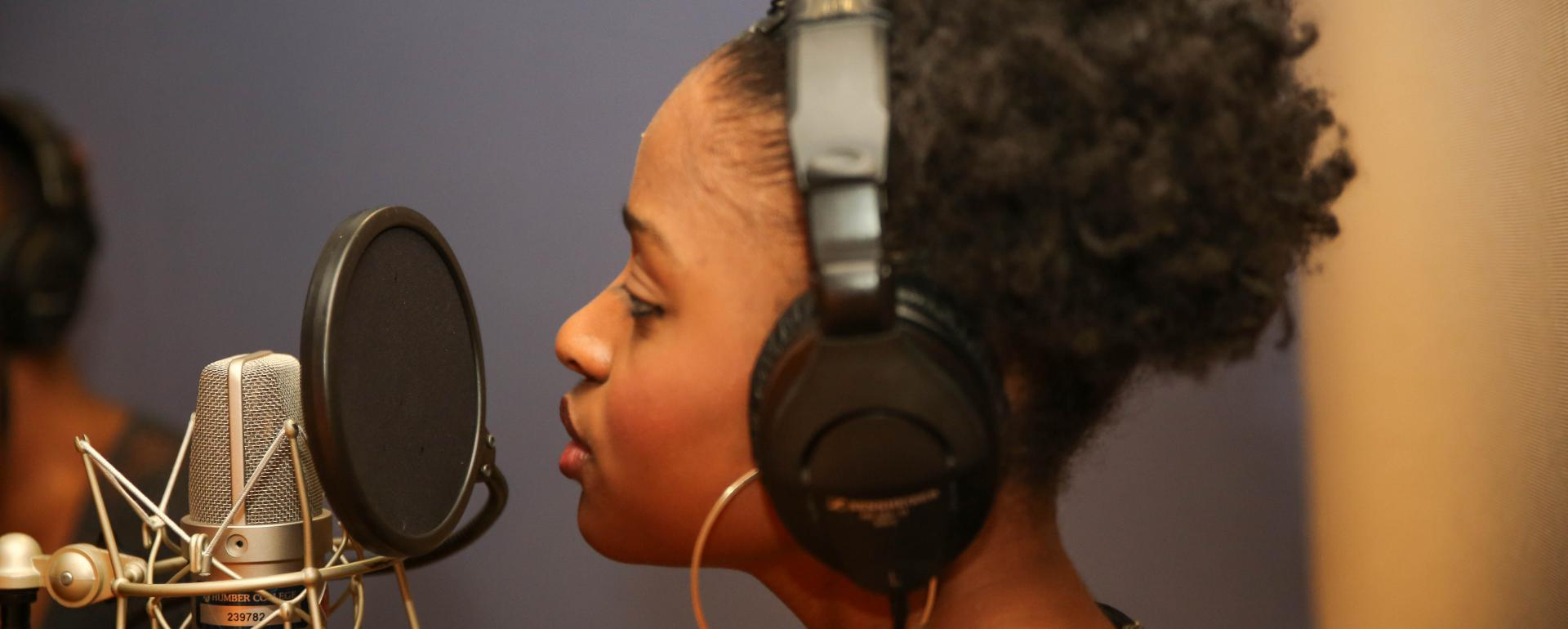 Woman singing into a microphone while wearing headphones