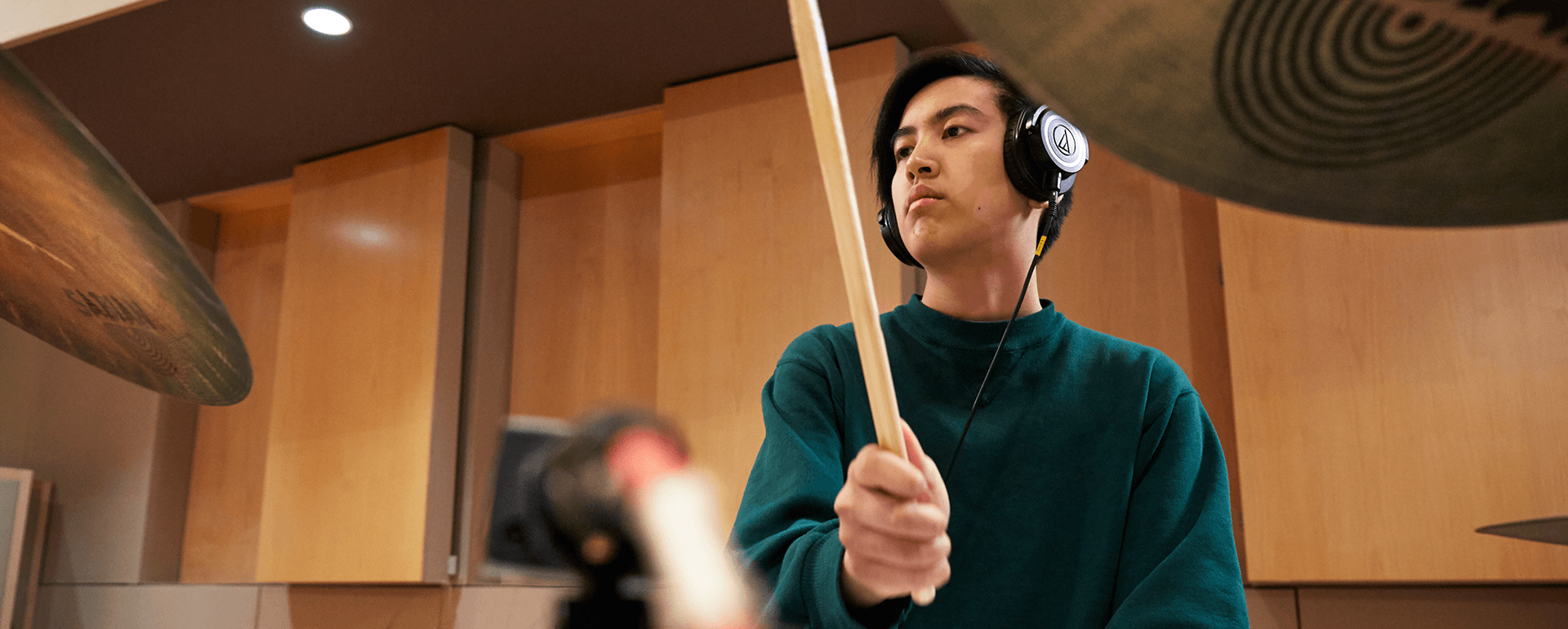 Young man playing drums while wearing headphones.