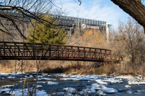 A walking bridge crosses a creek sprinkled with snow, with the glass facade of Humber's Learning Resource Commons visible in the background
