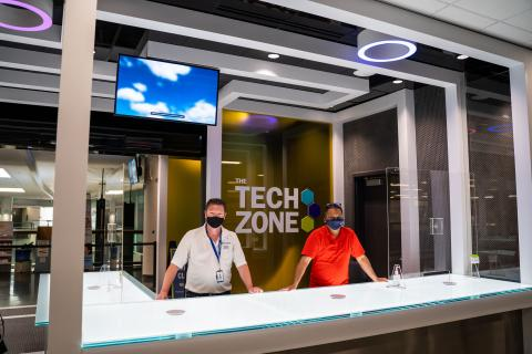 Two masked Humber IT staff members stand behind a big white desk at the futuristic Tech Zone