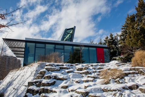 The Humber Arboretum building on a sunny day, surrounded by snow and footprints