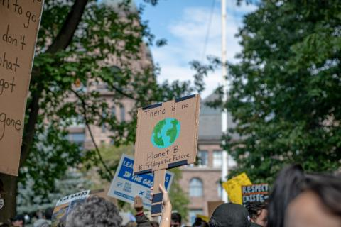 """People at a Climate Strike march fill a city street, holding protest signs. One of them says: """"There is no Planet B"""""""