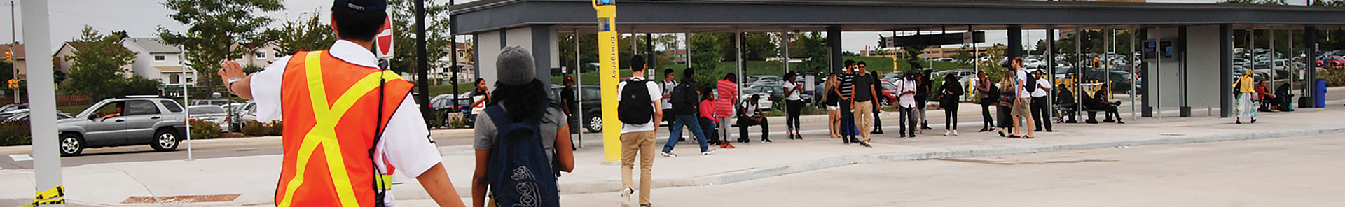 Guard stopping traffic to let students cross the road, in front of the bus terminal