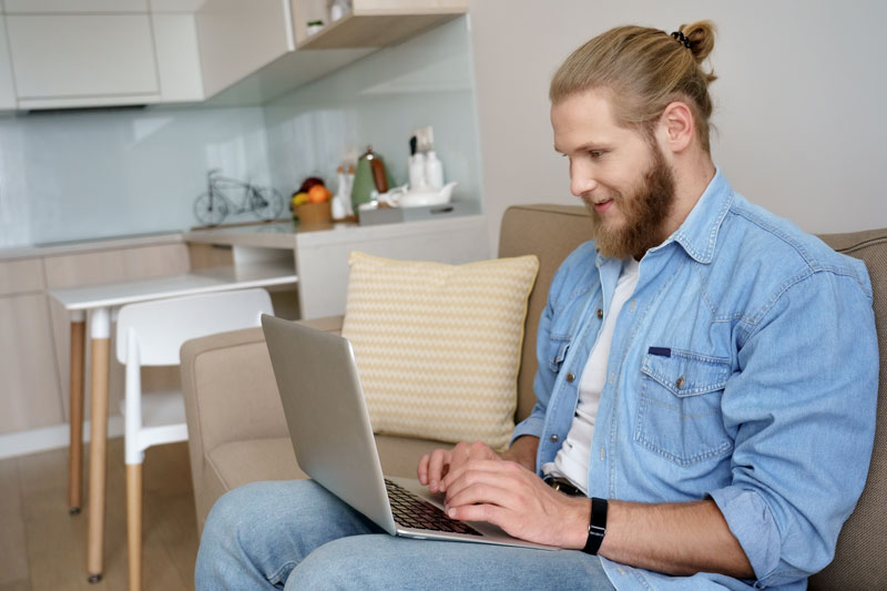 man sitting on a couch typing on a laptop keyboard