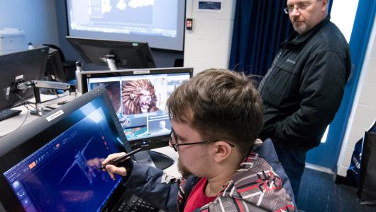 A guidance counsellors looks on as student works during a 3D Animation class.