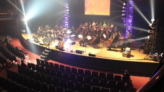 View of an orchestra on flood-lit event stage from the theatre balcony.