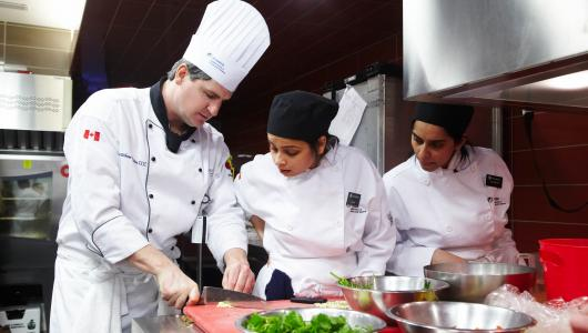 Students work with a professor in chef's uniform in Humber's culinary labs