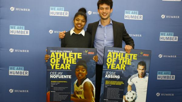 Ceejay Nofuente and Jesse Assing stand with their souvenir posters