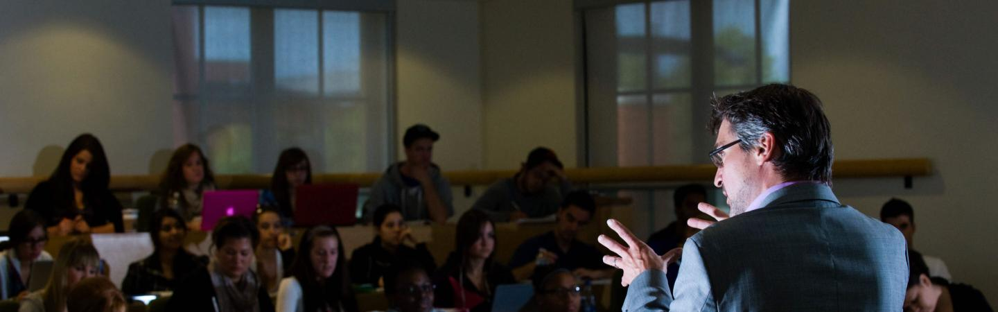 Professor stands at the front of a darkened classroom, speaking to adults