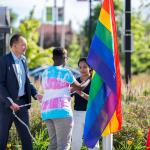 Three people raise the rainbow pride flag