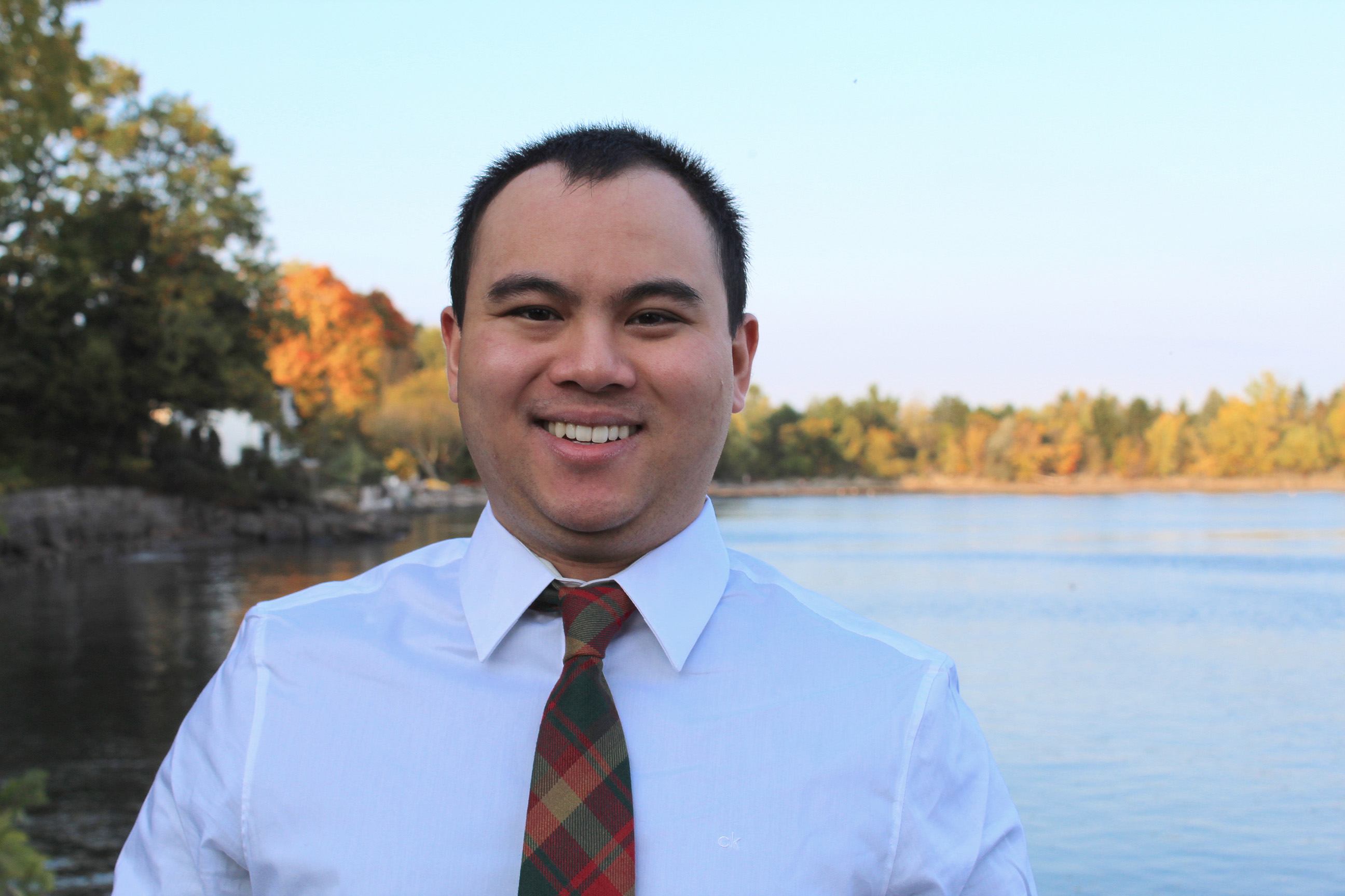 PR student Mathias Ho smiles, wearing a white shirt and red tie. There is a lake surrounded by colorful trees in the background