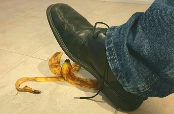 Close up of a person wearing a black shoe about to step on a banana peel