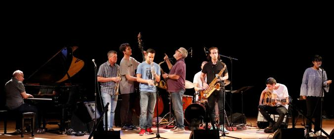 Group of student jazz musicians performing on stage with their faculty