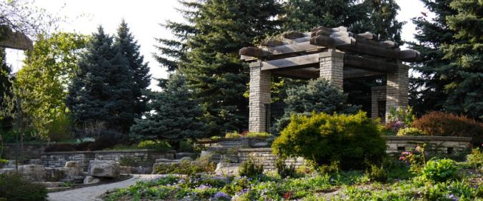 A stone and wood structure at the top of a waterfall in a lovely garden
