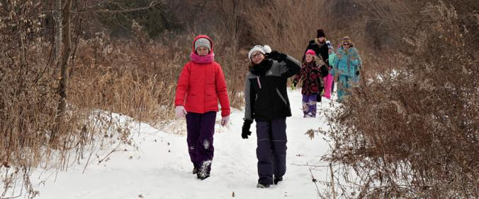 One girl waves to the camera as children walk through a snowy meadow