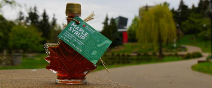 A maple syrup bottle sits on a plant stand with the Centre for Urban Ecology in the background
