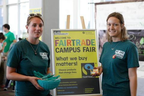 Student volunteers in front of a Fair Trade Campus Fair poster.