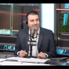 Sid Seixeiro sits at a news desk in a studio in front of a  microphone with a SN590 flag