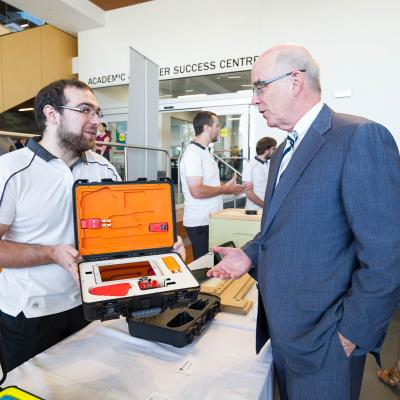 A Humber student shows a visitor a device built to help farmers and bee keepers track and manage environmental crop and hive conditions in an easy to use assembly.