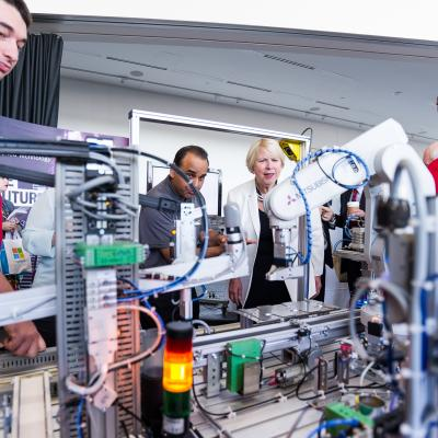 Humber students, Avery bird and Theo Willert, and Automation and Robotics program co-ordinator, Neal Mohammed, show the Honourable Deb Matthews some of the robotics student work with at Humber College.