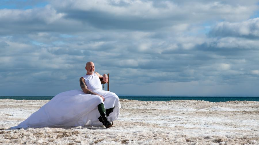 'Raise Hell' by Madeline Wallace is a photo of a person with a beard and a long white dress on a windy day at the beach