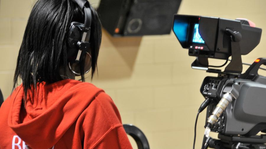 A Humber student operates a video camera with headphones on