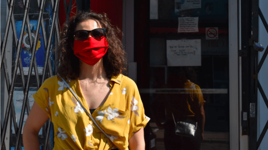 A Kensington Market visitor colour coordinates their red mask with their yellow shirt