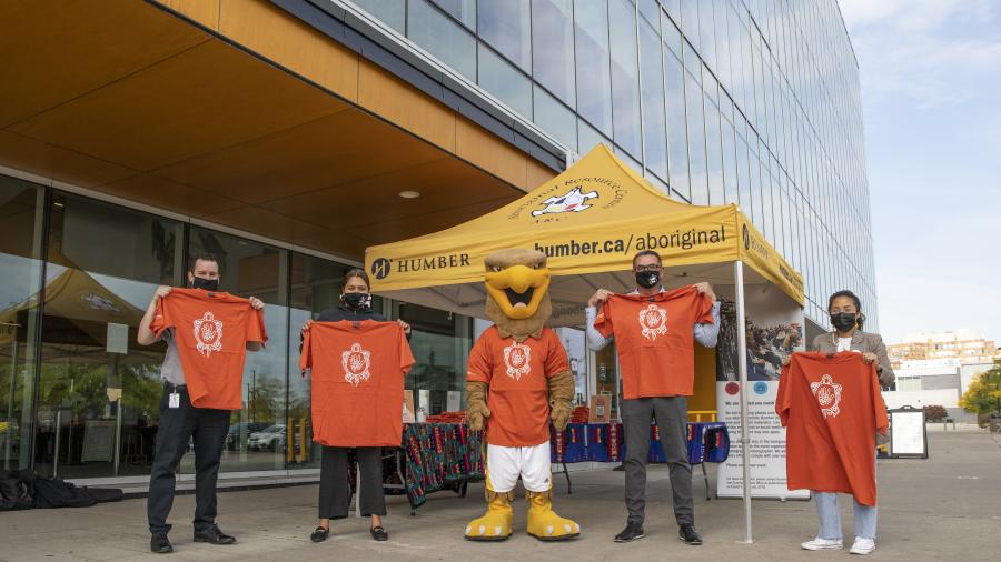 Five people stand outside a large building holding orange shirts.