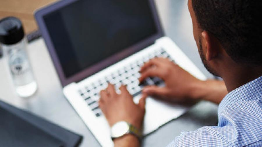 overhead view of a man sitting down at a laptop