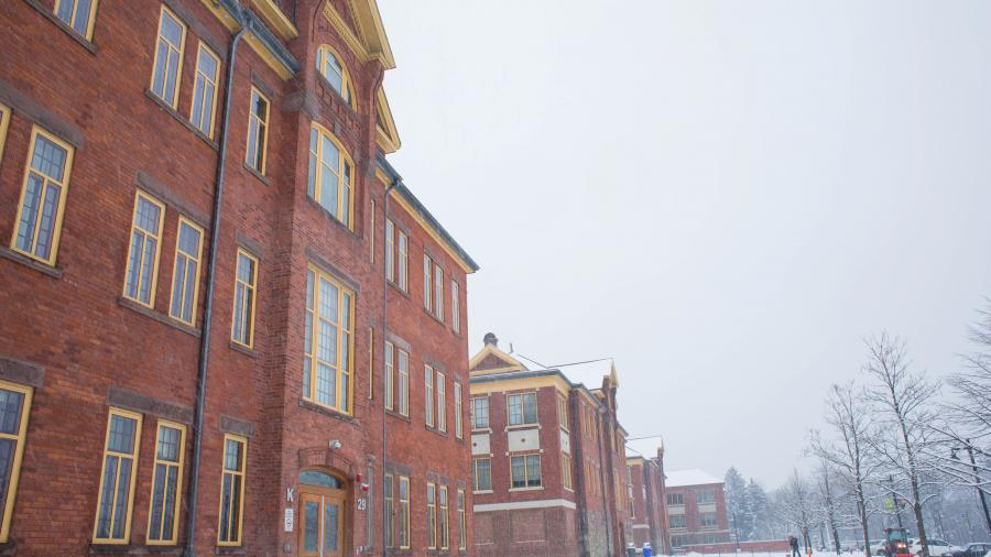 A brick building on Lakeshore campus seen from below, against a grey sky with snow on the ground