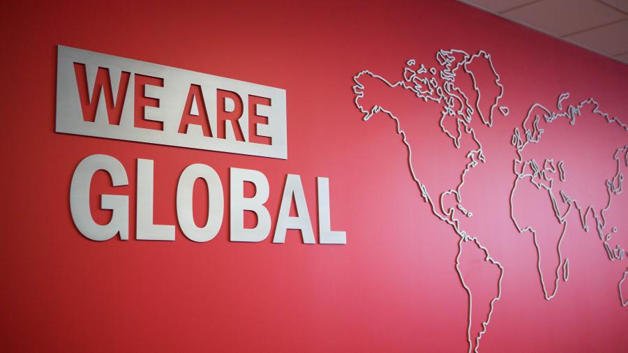 A red wall at Humber's International Centre with the words WE ARE GLOBAL printed beside a map outline