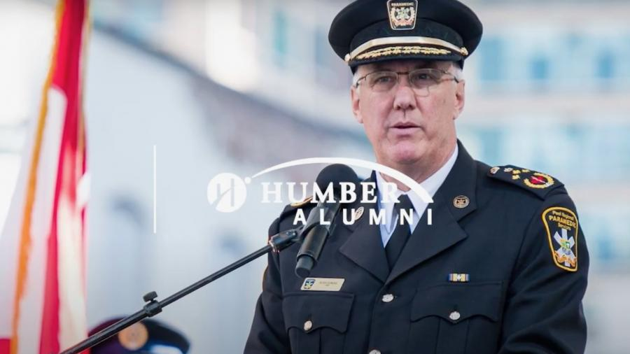 """Dundas stands at a podium in uniform with the Canadian flag in the background. The words """"Humber Alumni"""" are overlaid"""