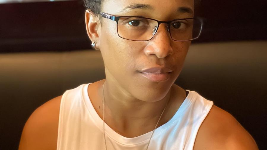 Krystal Moodie is seated, wearing a white sleeveless t-shirt and thin-framed glasses. She gazes sideways at the camera.