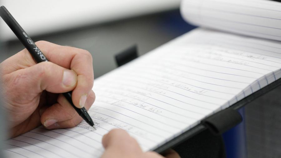 A hand is holding a black pen, writing on a small notebook, held by the other hand.