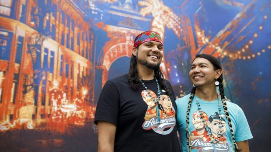 Anthony Johnson, left, and James Makosis, right, have their arms around each other, smiling and wearing long braids