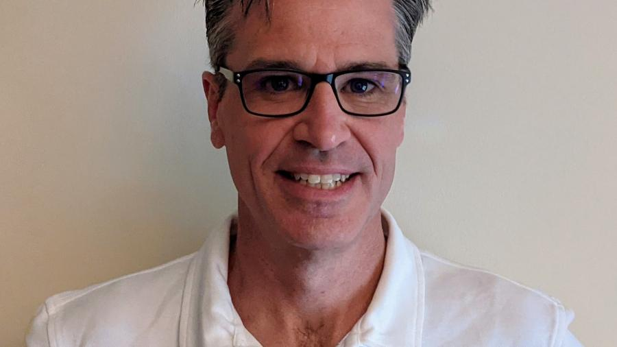 Professor Culum Canally smiles in a headshot, wearing a white button-up and black glasses in front of a beige wall.
