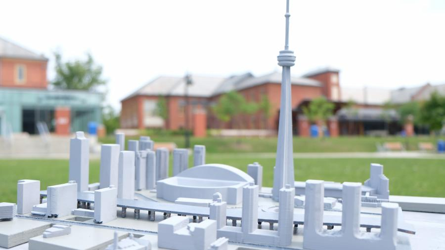 The interns' Tiny Town Model, grey skyscrapers and a tiny CN Tower is shown with the Lakeshore campus in the background