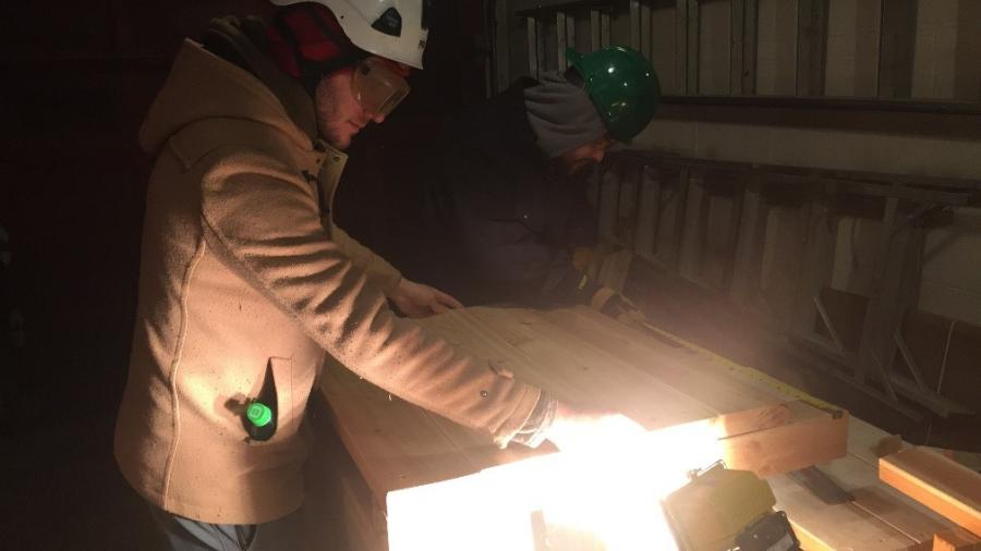 Students work on hydroponics table wearing hardhats
