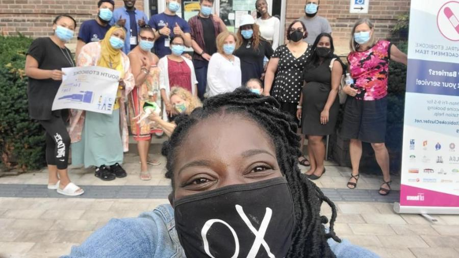The vaccination clinic team at Lakeshore stands with masks on behind a woman taking a selfie, centered in the frame.