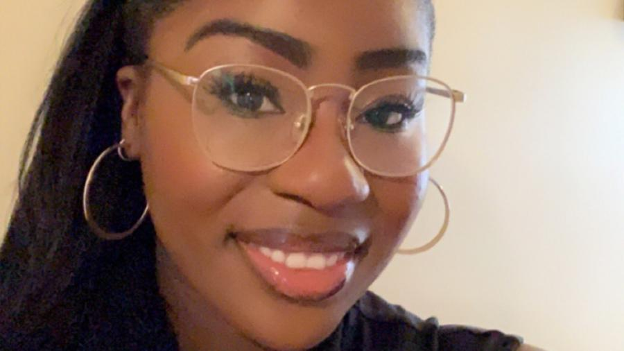 Michelle Ntiamoa smiles in a selfie. She is wearing nude lipgloss and large wire-framed glasses
