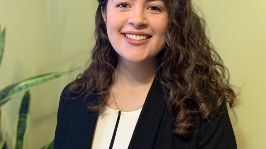 Nicole Pantaleo smiles in a headshot in a white shirt and black blazer. She has long curly hair parted on the side