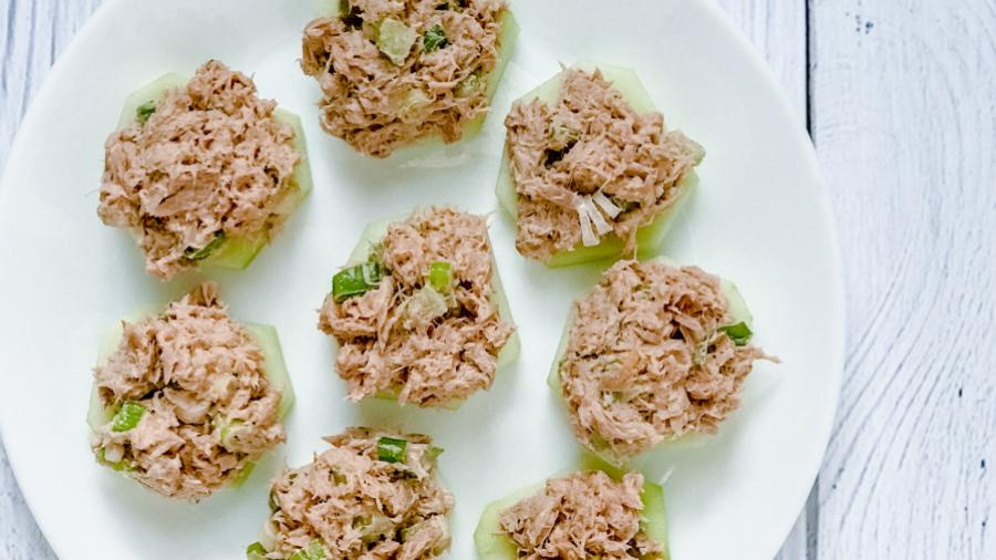 Several tuna sliders arranged on a white plate on a white table. The sliders are pink with tuna mixed with green onions