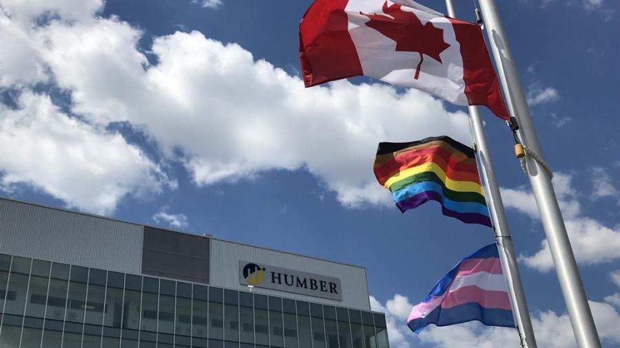 The Trans, Pride and Canadian flags are at half mast against a blue sky with puffy white clouds in front of Humber North's LRC