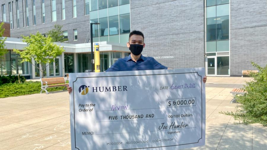 Newton Lew holds up a giant cheque for $5,000 from Humber College which hides most of his body.He's wearing a t-shirt and shorts
